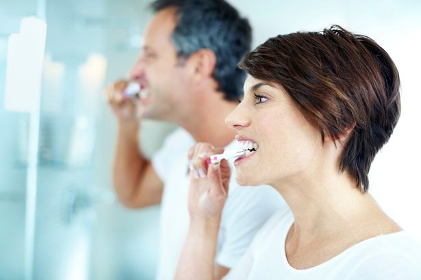 Couple brushhing their teeth