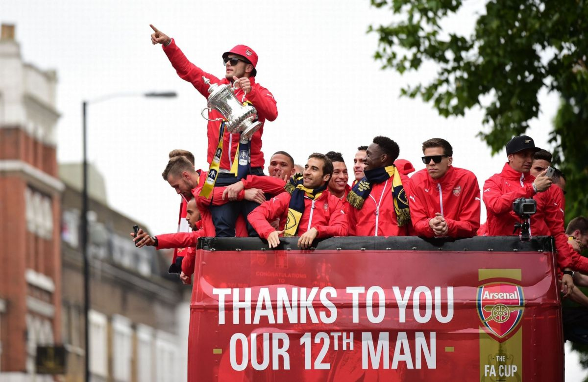 Jack Wilshere holds the trophy as he stands with team mates