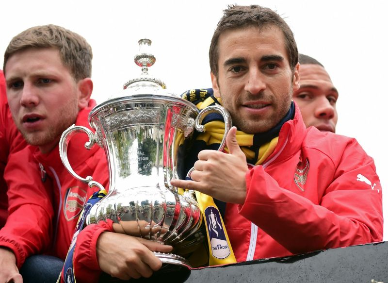 Mathieu Flamini holds the trophy