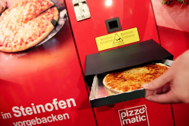 A hostess takes a pizza out of a Pizzomatic vending machine baking and selling pizzas on September 8, 2011 in Cologne
