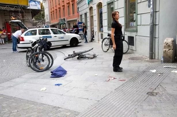 Police investigators stand at the scene where an SUV drove into pedestrians in the city center of Graz, Austria