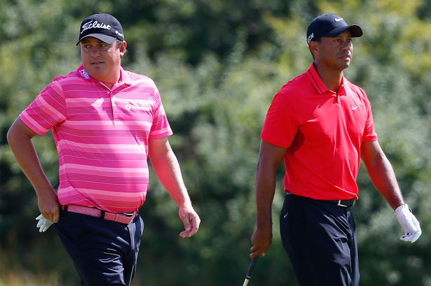 Tiger Woods of the United States walks with Jason Dufner of the United States