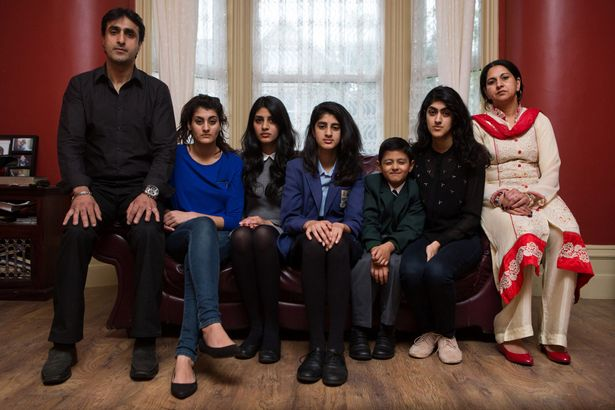 Nissar Hussain, 49, with his children, Anniesa, 21, Miriam, 17, Leena, 14, Isaaq, 7, Sarah, 19, and wife Kubra, 45, pictured at their home in Bradford, West Yorkshire
