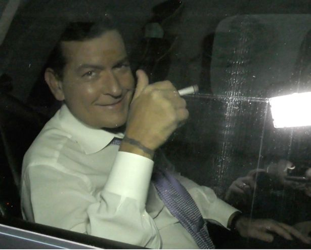 Charlie Sheen bites on finger and has a cigarette as he gives thumbs up in NYC