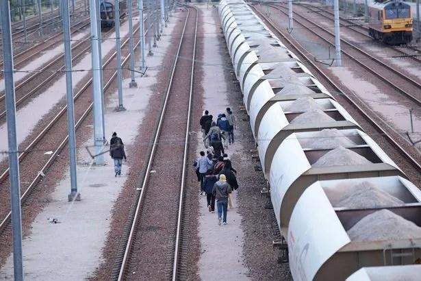 Los migrantes hacen su camino a lo largo de vías cerca del Eurotúnel