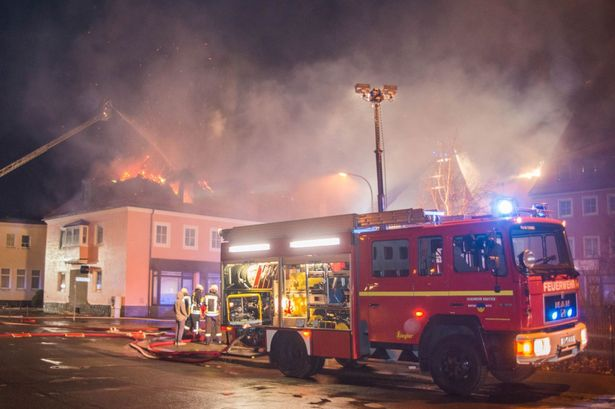 Fire fighters try to extinguish a fire at a former hotel that was under reconstruction to become a home for asylum seekers