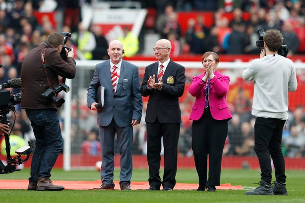 "Sir Bobby Charlton and wife Norma applaud fans as the newly renamed South Stand ""Sir Bobby Charlton stand"" is unveiled"