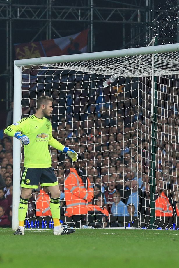 A bottle flies toward Manchester United goalkeeper, David de Gea