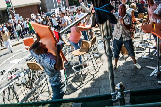 A Muslim protester attacks an elderly gentleman with a table enjoying a drink in the sun outside a Cardiff bar