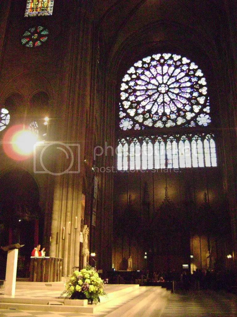 Priest saying mass at Notre Dame (rose window)