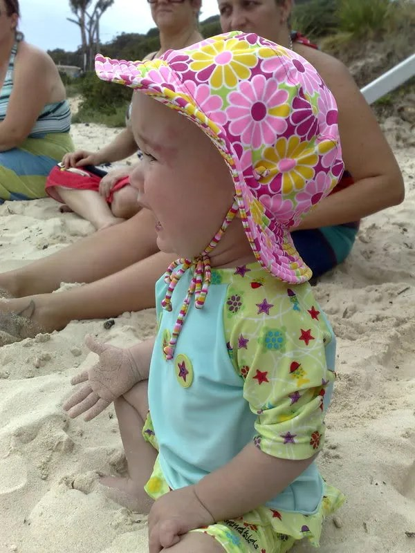 not liking the sand on her hand