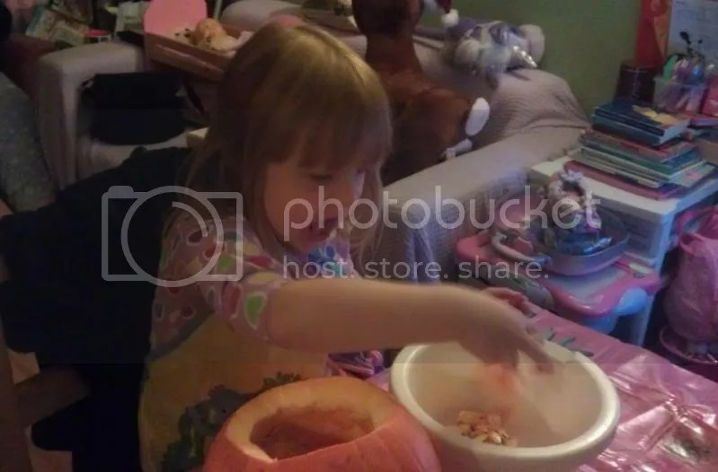 Evie scooping out the pumpkin