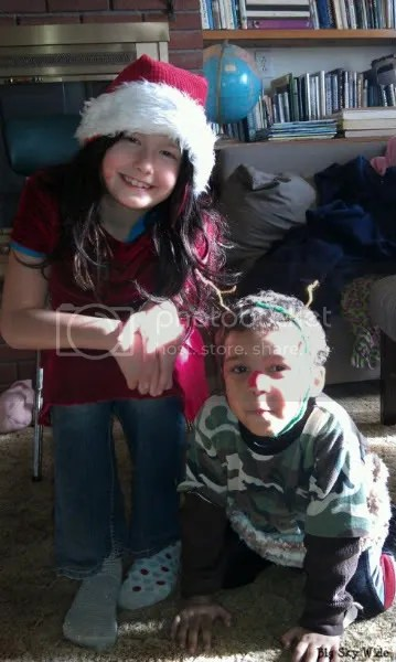 Girl wearing Santa hat and boy down on all fours wearing reindeer antlers and red nose. (Photo by Big Sky Wide)