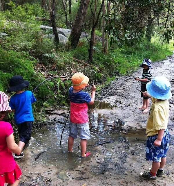 children playing in a creek with sticks - safe, fun and educational!