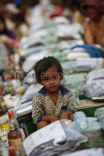 A girl sits among other Cambodian displaced people