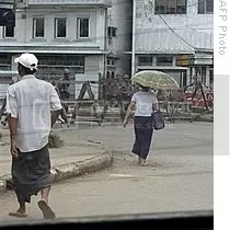 Handout photo received and taken on 18 May 2009 from the Democratic Voice of Burma shows people walking past Myanmar soldiers manning a road block in Rangoon