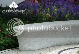 Ghế chất liệu granito đặt cạnh vườn hoa.