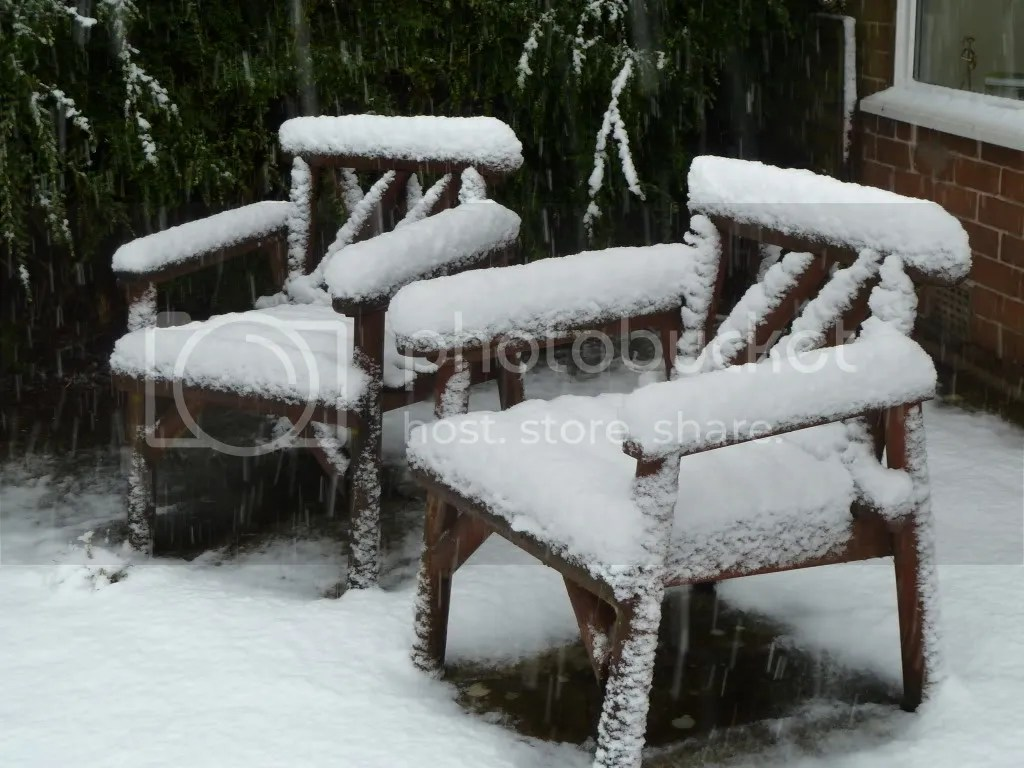 two chairs covered in snow