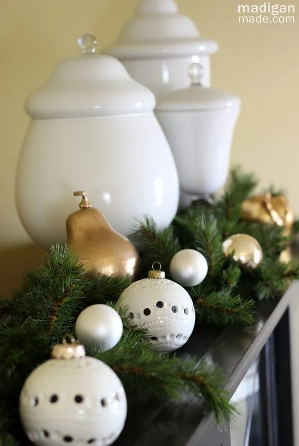 Lovely white ornaments mixed with evergreens - part of the holiday home tour at madiganmade.com