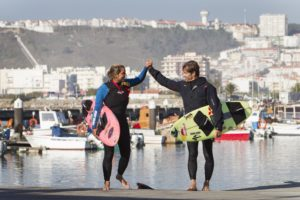 Maya Gabeira and Carlos Burle celebrating after surfing at Praia do Norte in Nazare, Portugal on November 14, 2015
