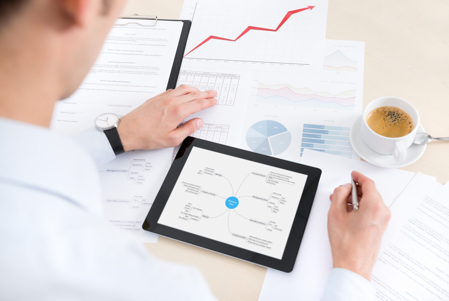 Businessman at the workplace working with documents and using modern apple ipad with mind map graphic.