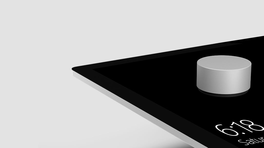 Image of Surface Dial on top of a touch screen displaying the time.
