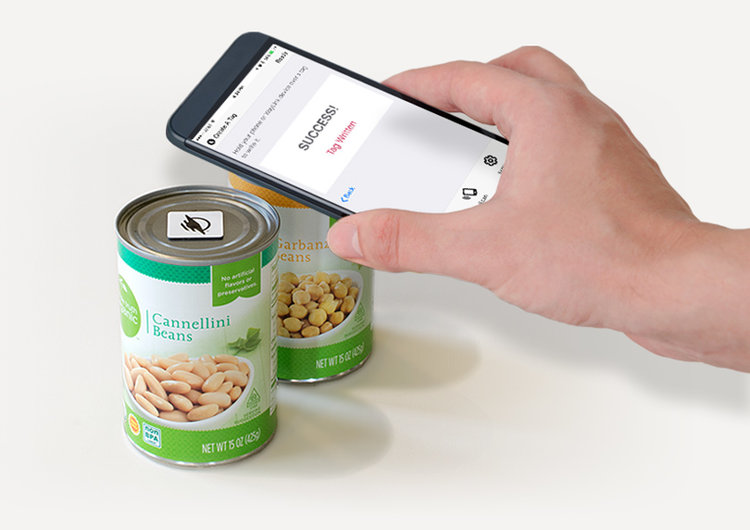 Image of hand with smart phone scanning NFC tag.