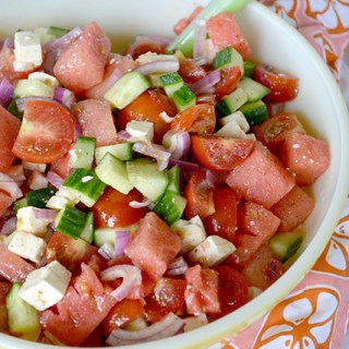 Large serving bowl of Watermelon Tomato Feta Salad on a colorful place mat.