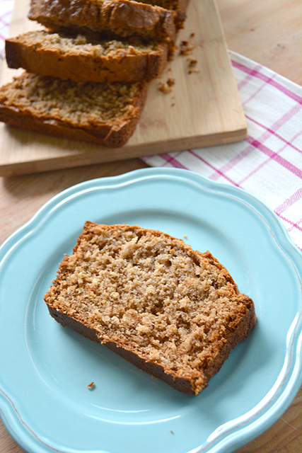 slice of banana oat bread on a blue plate next to a sliced loaf of bread