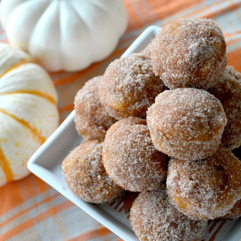 Plate of Mini Pumpkin Donut Muffins on plaid napkin next to small white pumpkin with text overlay