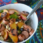 white bowl of sausage and peaches with festive mexican cloth in background