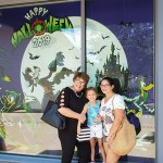 2 woman and a little girl standing in front of Halloween display at World of Disney in Disney Springs