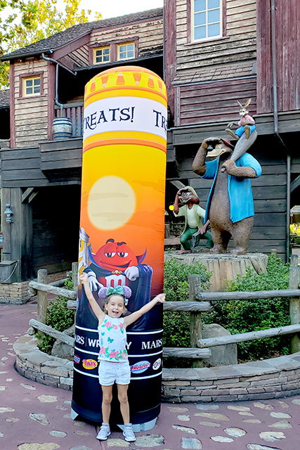 Young Girl standing in front of Trick of Treat Balloon at Disney Halloween Party