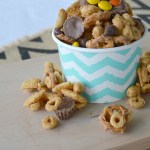 Patterned paper cup overflowing with Peanut Butter Lovers Chex with snack mix scattered around the container