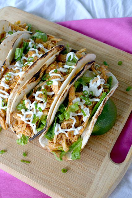 angled view of chicken tacos on cutting board