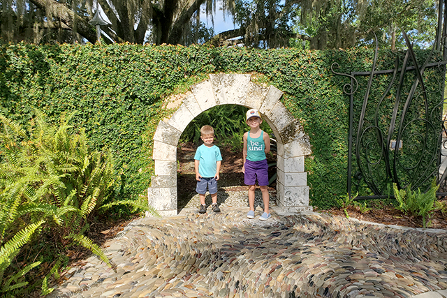 Little boy and Little girl standing under stone arch in a ivy covered wall