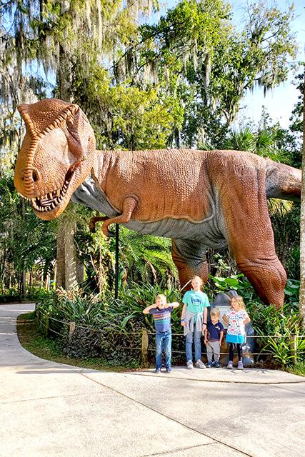 Tyrannosaurus Rex poses with four kids