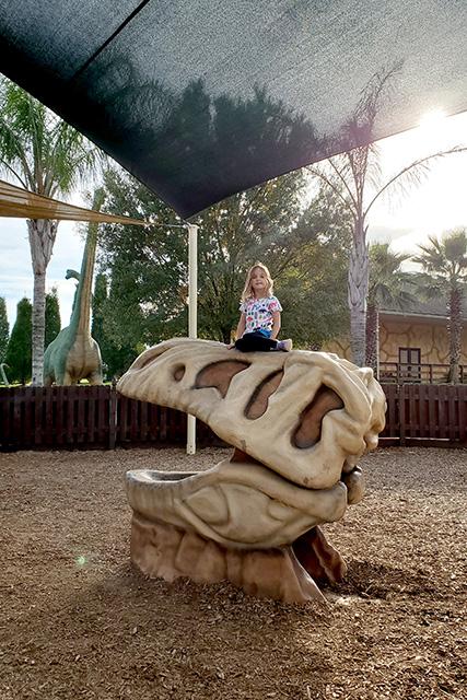 girl sits on dinosaur skeleton head