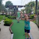 girl jumps for joy as she make a hole in one at pirate themed miniature golf facility