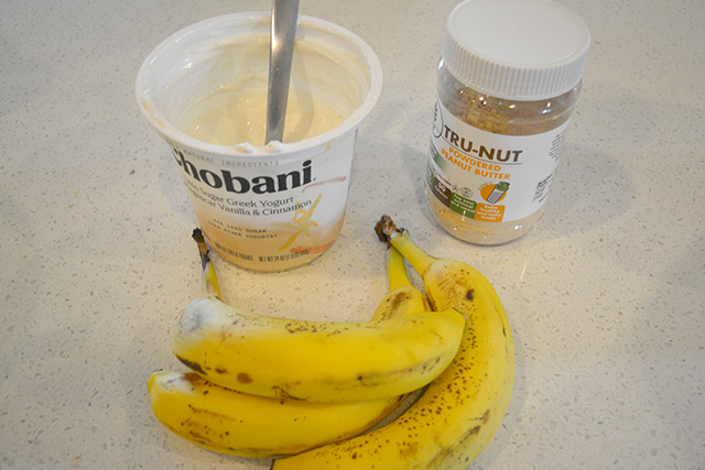 3 bananas, peanut butter powder, and a large container of Greek yogurt