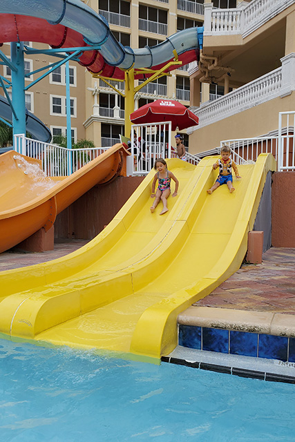 Little girl and boy sliding down yellow water slide at water park