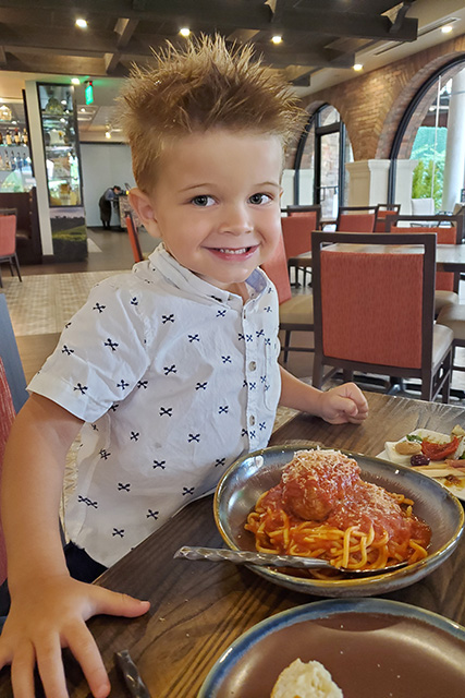 Little boy with spiky hair excited about big bowl of spaghetti and meatballs