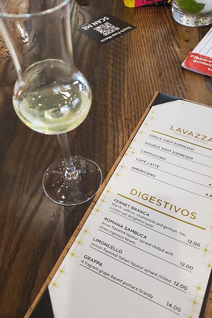 glass of limoncello next to dessert menu