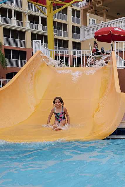 Little girl going down yellow slide at a resort pool