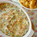 Baked Cheesy Spinach Artichoke Dip with a bowl of corn chips next to casserole dish of dip