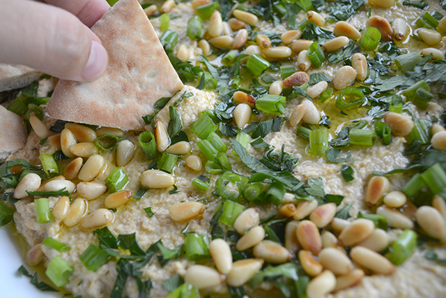 Pita being dipped into Homemade Hummus Toasted Pine Nuts