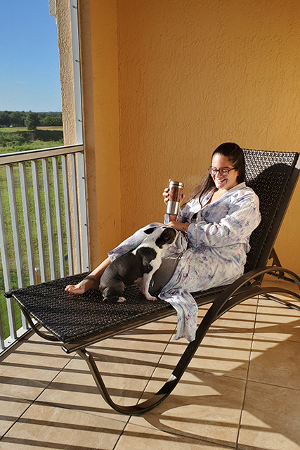 Woman sitting on chaise lounger with cup of coffee in hand and dog on lounger with her
