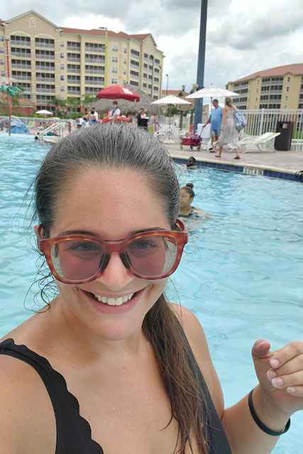 Selfie of a brown haired woman wearing sunglasses and a black bathing suit in a pool