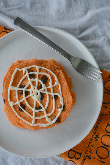 view from above of Orange Chocolate Chip Pancakes with a spider web design on top with cream cheese frosting on a white plate with a halloween themed napkin