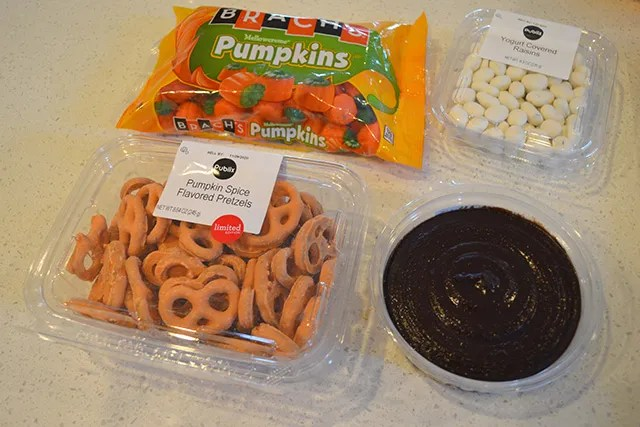 containers of mini candy pumpkins, yogurt covered raisins, chocolate covered pretzels, and dessert hummus